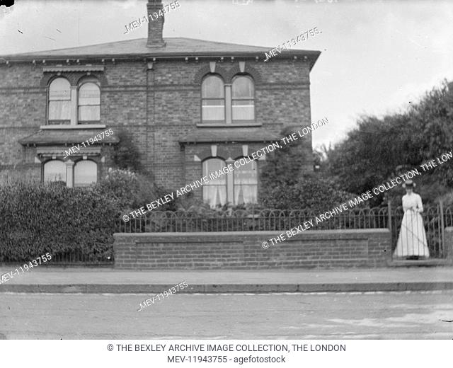 Lady standing inside the front garden gate in a house on Woolwich Road