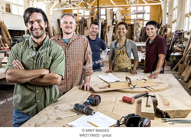 Team of multi-racial factory workers standing next to a work station in a large wood working factory