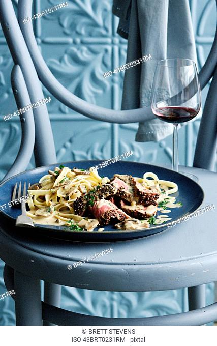 Bowl of beef stroganoff with wine