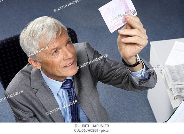 Businessman checking a 500 euro note