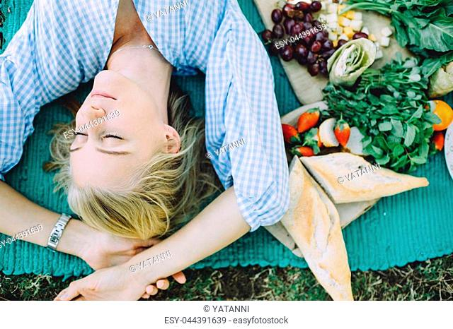 Young woman relaxing at summer picnic lying on mat with healthy food