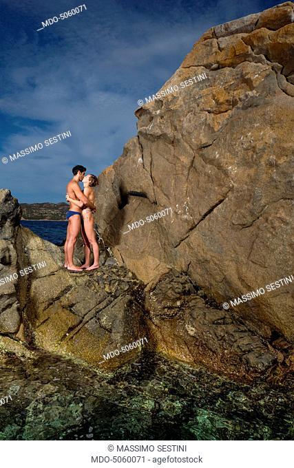 The swimmers Federica Pellegrini and Filippo Magnini kissing each other on the rocks of the promontory of Capo Coda Cavallo. Olbia-Tempio, Italy