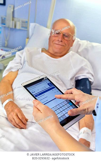 Nurse entering data of a patient on the tablet, hospital room, Hospital Donostia, San Sebastian, Gipuzkoa, Basque Country, Spain