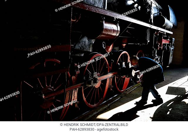 Former railwaymen Werner Kruger shines the bright red wheels of a steam locomotive of series 52-4900 at the Museum of the Deutsche Bahn in Halle/Saale, Germany