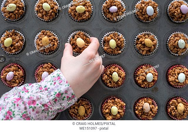 A childs hand selecting an Easter chocolate krispy cake