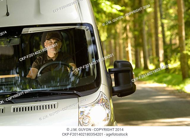 Postal delivery courier in van on his way delivering package