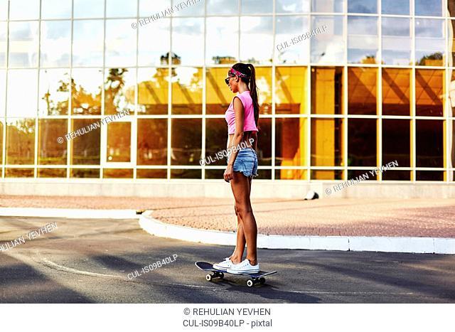 Young woman skateboarding along road