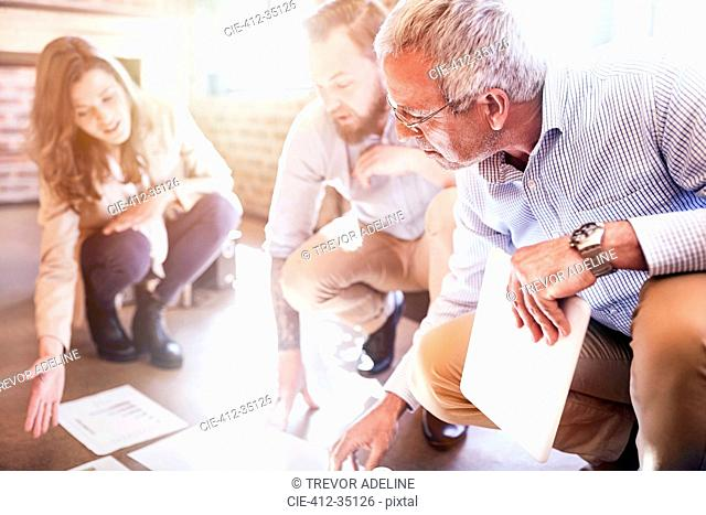 Business people reviewing and discussing paperwork on sunny office floor