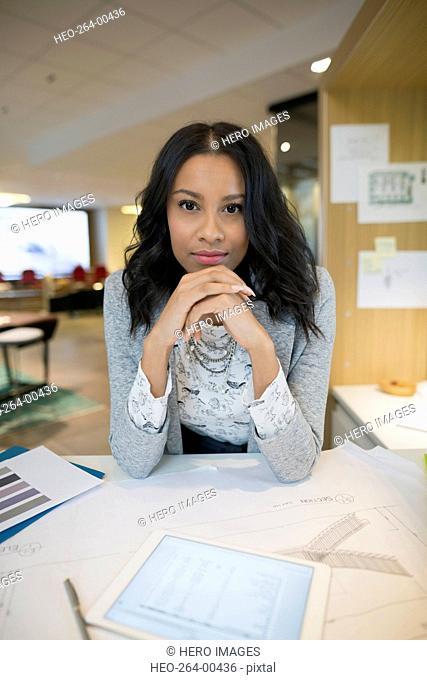 Portrait of confident young female architect at desk