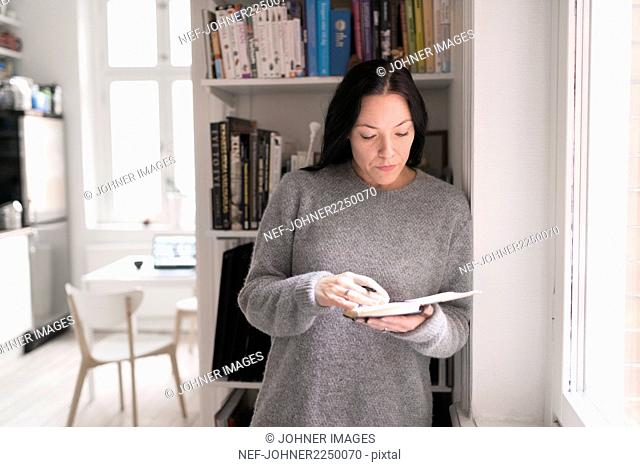 Woman holding note pad, standing by window