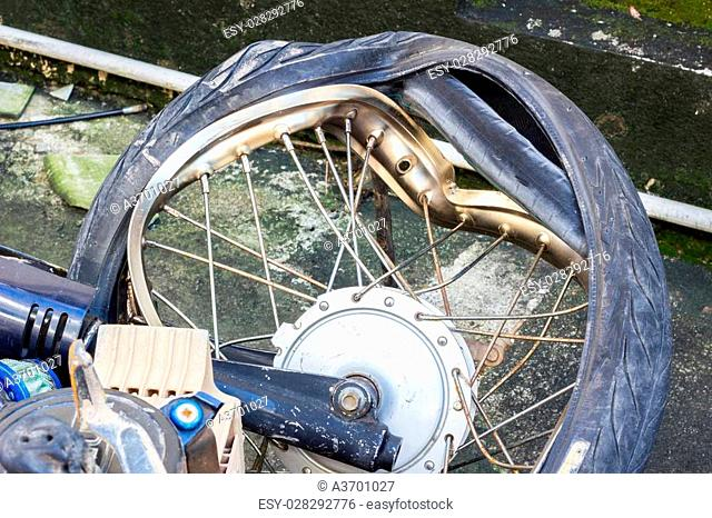 broken wheel of crashed motorcycle, accident on the road