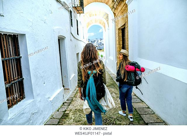 Spain, Andalusia, Vejer de la Frontera, two young women walking in the alley El Callejon de las Monjas