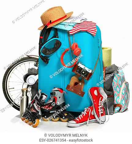 The blue suitcase, sneakers, clothing, hat, and retro camera on white background. The travel, tourism and holidays concept
