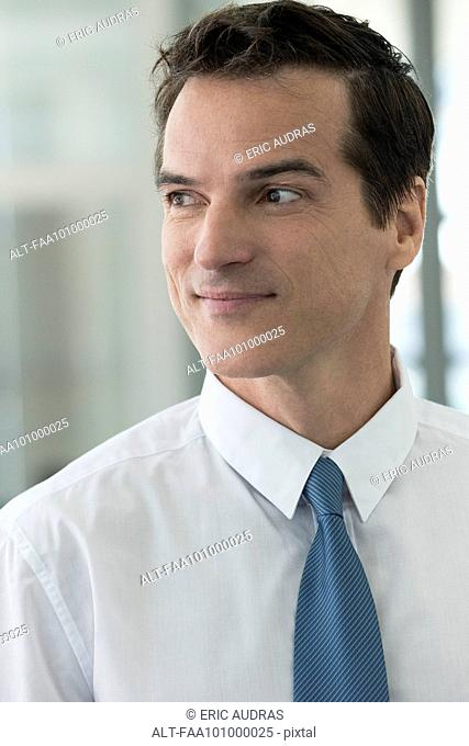Businessman looking away in thought, smiling, portrait