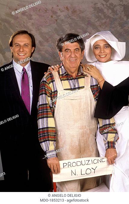 Italian director Nanni Loy, Italian TV presenter Gerry Scotti and Italian showgirl Mara Venier (Mara Provoleri) posing on the set of the TV show Candid Camera