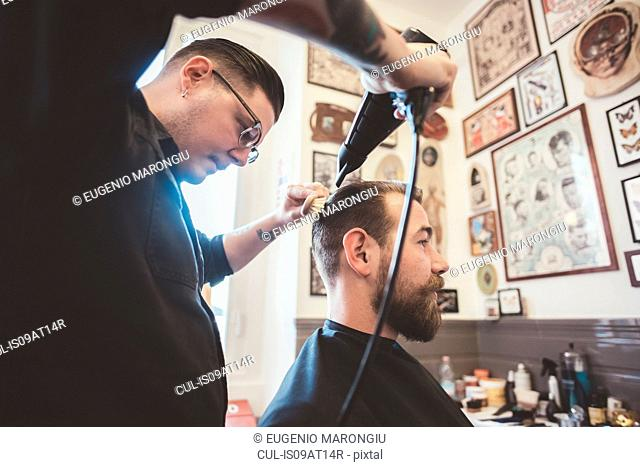 Barber blow drying clients hair in barber shop