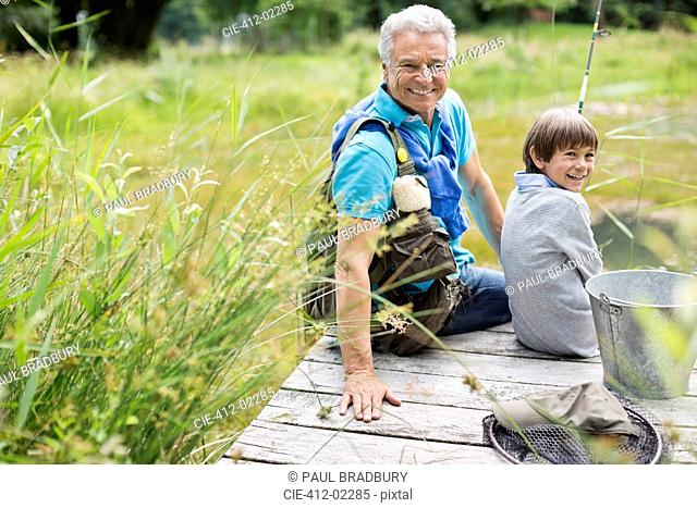 Man fishing with grandson on wooden dock