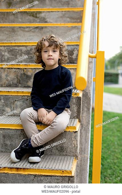 Portrait of boy sitting on stairs