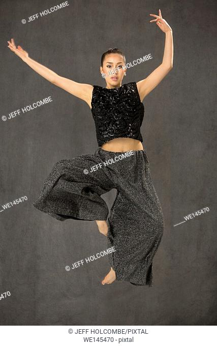 Attractive young woman dancing full length, in black top and baggy gray pants in studio shot on gray background