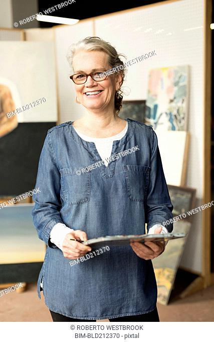 Caucasian artist smiling in studio
