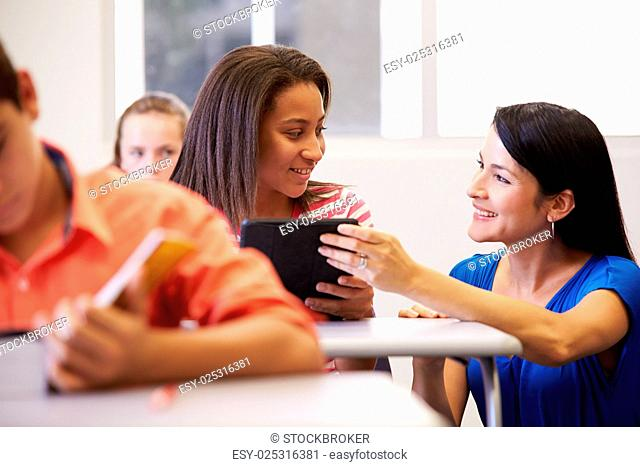 Teacher Helping Female High School Student In Classroom