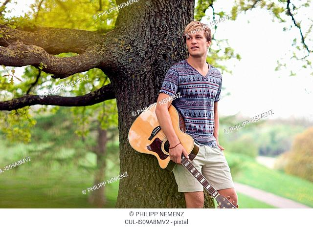 Portrait of young man leaning on tree trunk with guitar