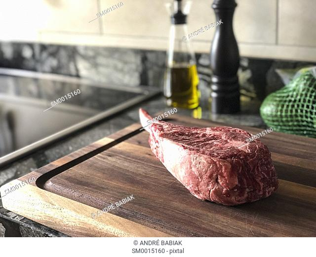 Horizontal close up photo of bone-in ribeye steak with oil dispenser and pepper mill in the background on a kitchen counter