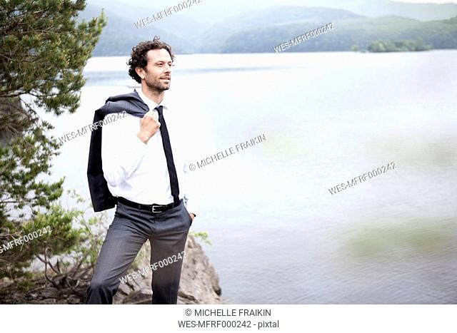 Germany, Rur Reservoir, relaxed businessman at lakeshore