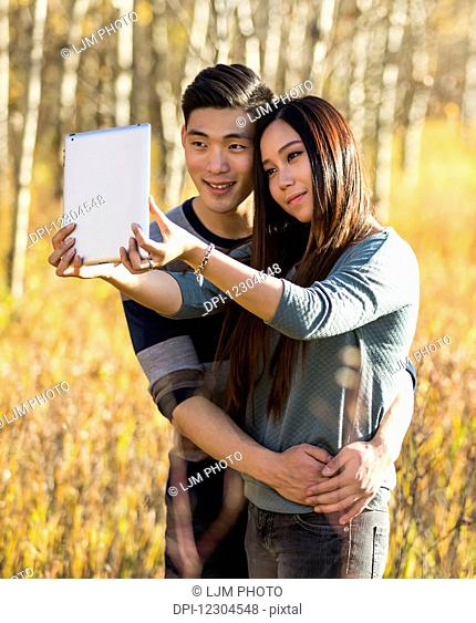 A young Asian couple enjoying quality time together outdoors in a park in autumn and taking self-portraits using a tablet in the warmth of the sunlight during...