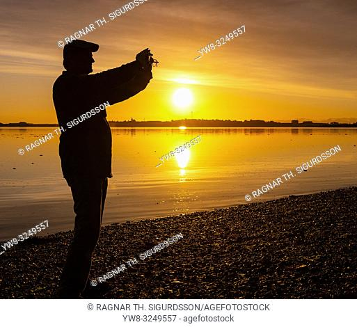 Man taking a picture at sunset, Borgarnes, Western Iceland