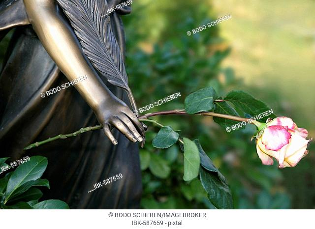 Angel Statue, rose in hand, cemetery