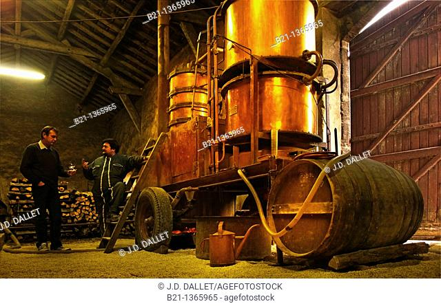 Olivier Gessler, with a 'boulleur de cru' alcohol burner in front of alambic during the distillation of the armagnac, Domaine de Joÿ wines and armagnac estate