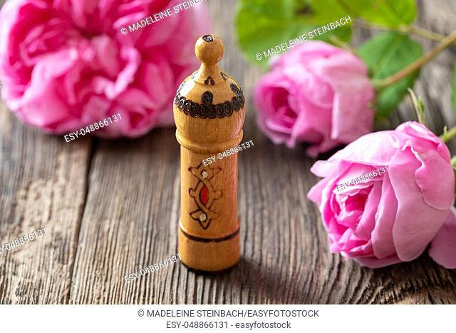 A bottle of essential oil with fresh cabbage roses