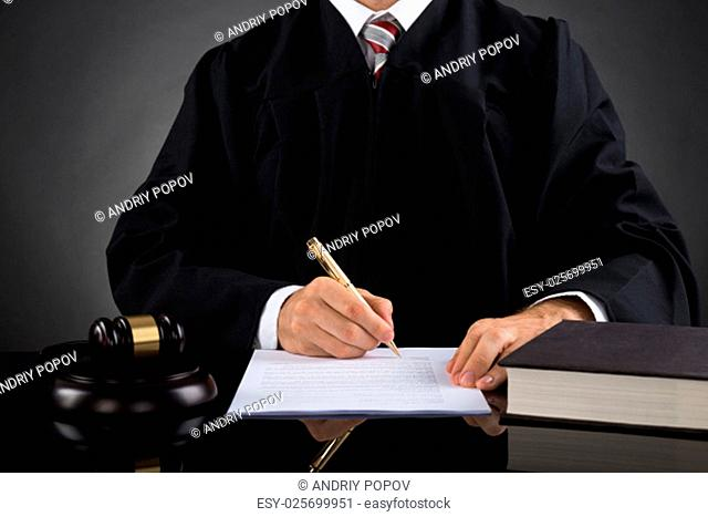 Close-up Of Judge Writing On Paper With Pen In Courtroom