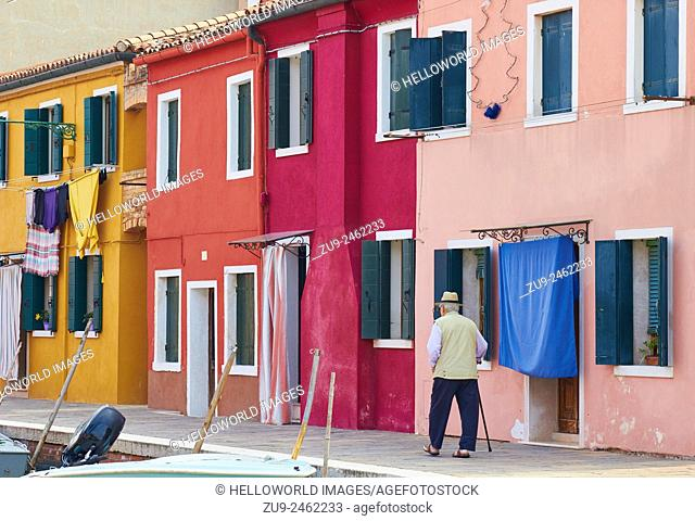 Elderly man walking past colourful row of houses, Burano, Venetian Lagoon, Veneto, Italy, Europe