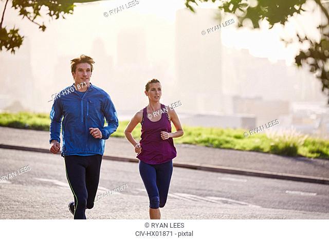Runner couple running on sunny urban city street