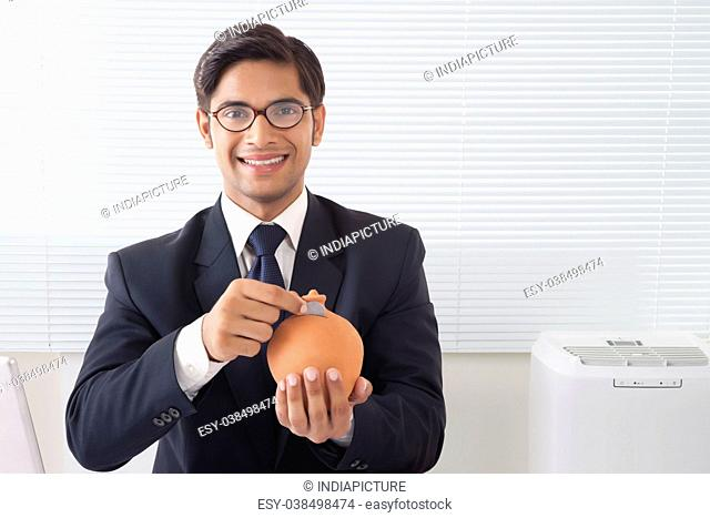 Happy looking young professional man dropping coin in clay saving pot in office room