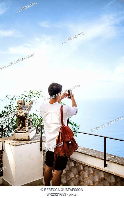 Rear view of man standing at railing and clicking selfie against sky