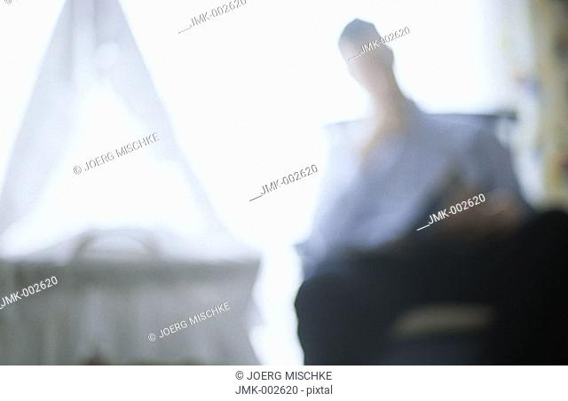A young man, 25-30 30-35 35-40 years old, sitting in a rocking chair in the nursery, next to the cradle, reading, blurred