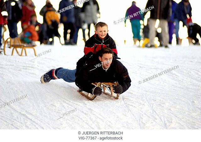 Father going sleding with his son. - GERMANY, 01/01/2004