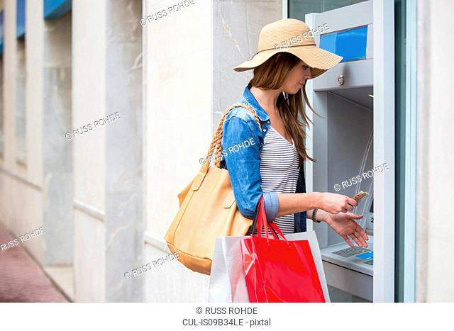 Woman withdrawing cash from cash machine