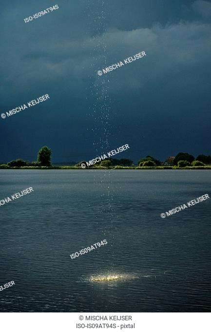 Heavy rainfall and droplets splashing into lake during thunderstorm