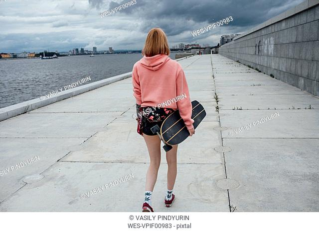 Rear view of young woman holding carver skateboard walking at the riverside