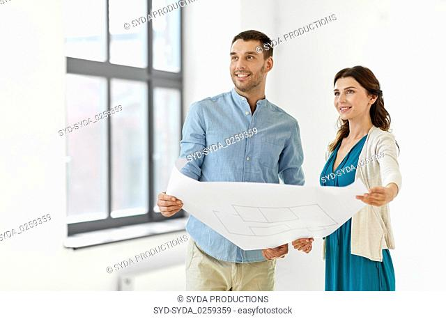 happy couple with blueprint at to new home