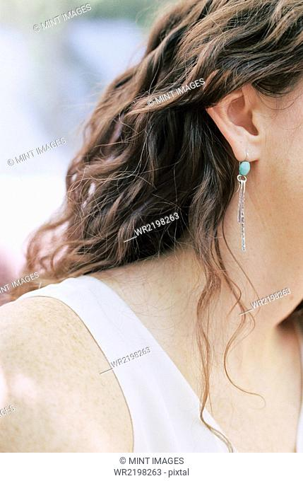 Close up of a woman wearing a silver and turquoise earring