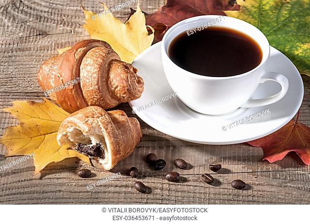 Coffee with a croissant on a wooden table. Grains of coffee and maple leaves on the table