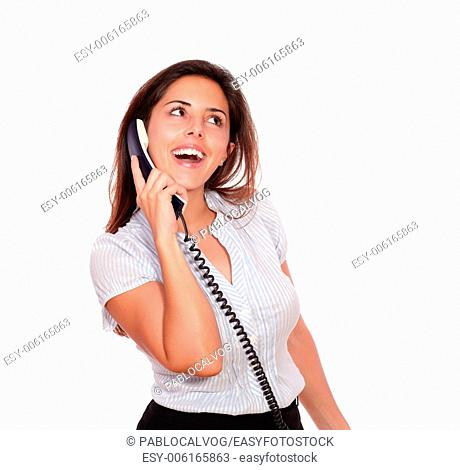 Portrait of a smiling hispanic female talking on phone while looking up on white background - copyspace