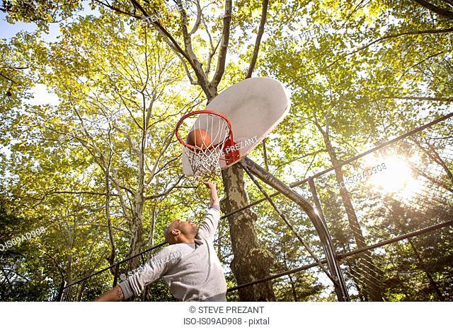 Young man scoring basketball goal