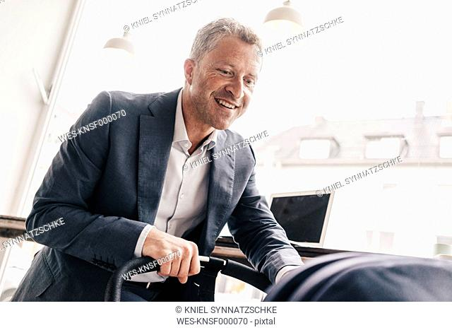 Businessman sitting in cafe with pram