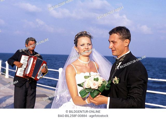A wedding pair with the Cazino restaurant on the shore of the Black Sea in the coastal city of Constanta in Romania